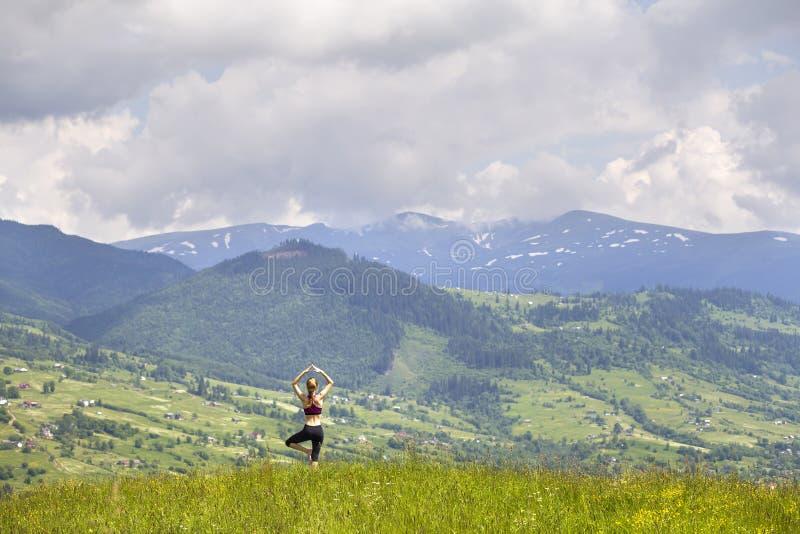 Aantrekkelijke slanke jonge vrouw die yogaoefeningen in openlucht op achtergrond van groene bergen op zonnige de zomerdag doen stock afbeeldingen