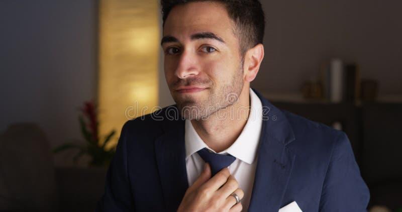 Aantrekkelijke Spaanse mens die zijn band bevestigen stock foto