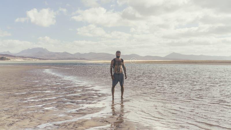 Aantrekkelijke spier gebaarde mens die zich op de overzeese kust bij zonsopgang bevinden Zijportret van het gezonde jonge gebaard stock foto's