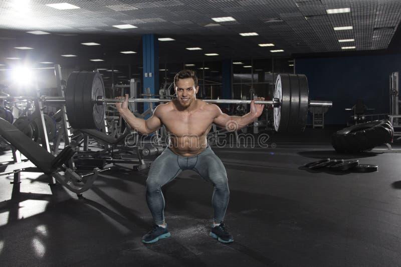 Aantrekkelijke spier shirtless atleet die zware hurkende exercis doen royalty-vrije stock foto's
