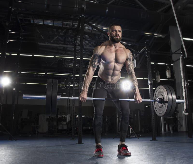 Aantrekkelijke spierbodybuilder die deadlifts in moderne gymnastiek doen C stock afbeelding
