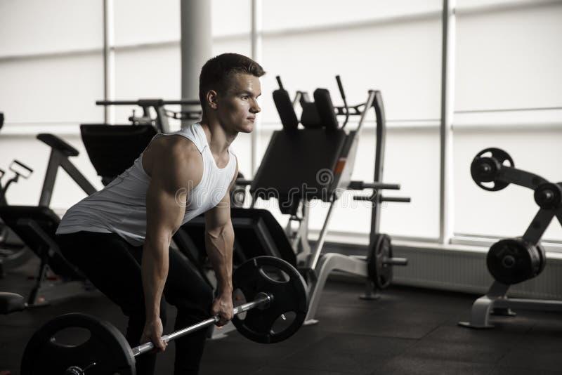 Aantrekkelijke spierbodybuilder die zware deadlifts in modern geschiktheidscentrum doen royalty-vrije stock afbeelding