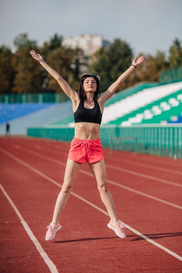 Aantrekkelijke sportieve donkerbruine vrouw in roze borrels en hoogste het doen training met springtouw in zonstralen bij het sta royalty-vrije stock afbeelding