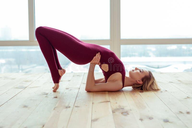 Aantrekkelijke sportieve vrouw die helpen met handen terwijl het overspannen van haar lichaam stock afbeelding