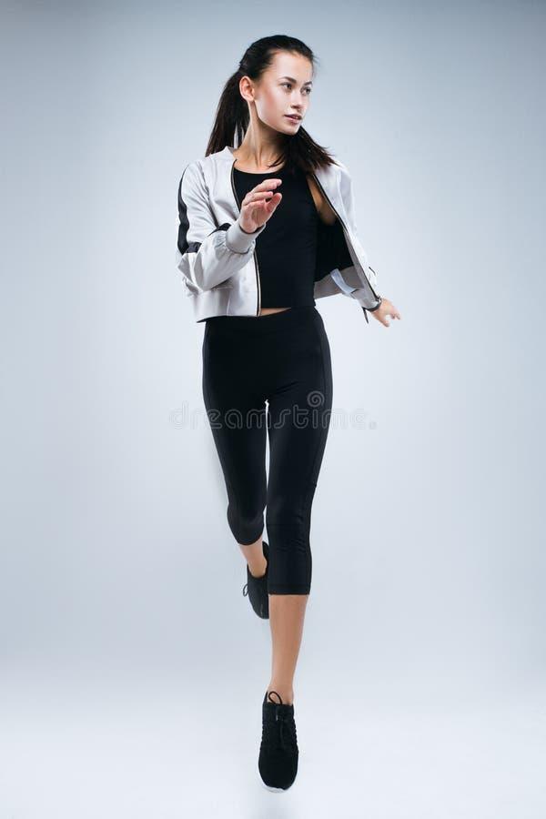 Aantrekkelijke sportvrouw die die en in studio lopen springen over grijze achtergrond wordt geïsoleerd royalty-vrije stock fotografie