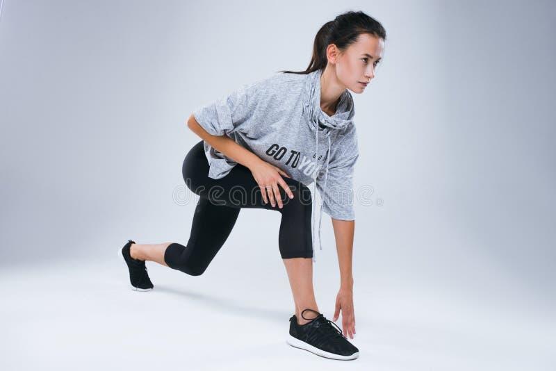 Aantrekkelijke sportvrouw die over grijze achtergrond voorbereidingen treffen te lopen stock foto