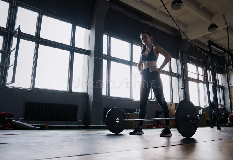 Aantrekkelijke sterke spier vrouwelijke bodybuilder die op zwaar werk berekende hurkzit doen die barbell bij de crossfitgymnastie stock fotografie