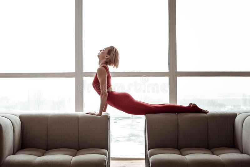 Aantrekkelijke sterke vrouw die in heldere rode uitrusting yoga uitvoert stock foto's