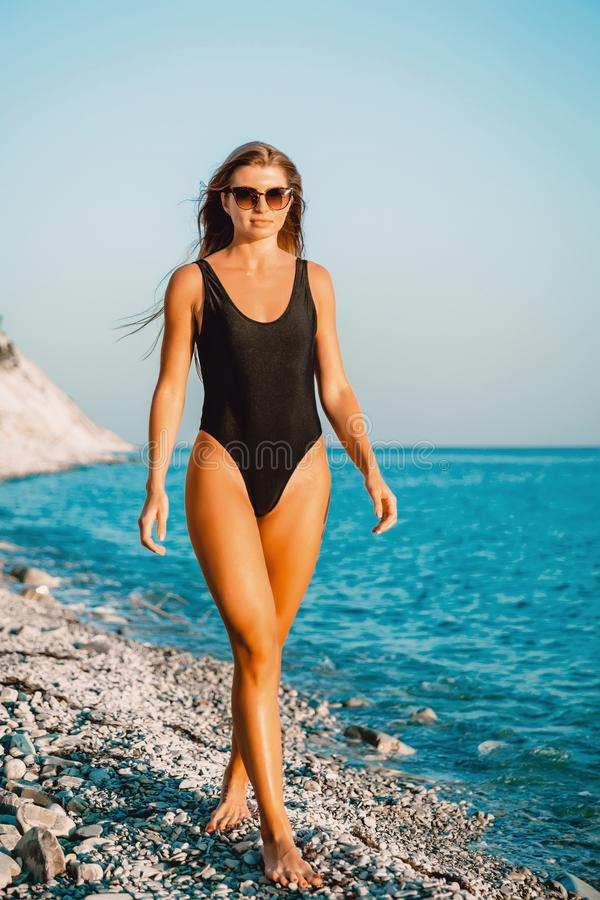 Aantrekkelijke tan vrouw in zwart zwempak op strand royalty-vrije stock fotografie