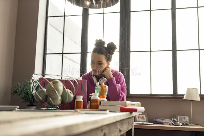 Aantrekkelijke tiener die met oortelefoons op hals in keuken bestuderen royalty-vrije stock foto's