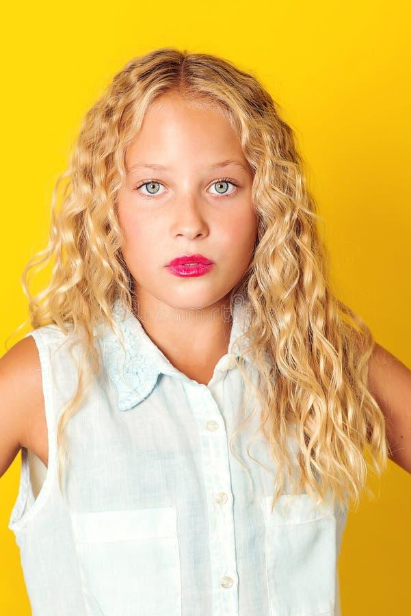 Aantrekkelijke tiener met blonde golvend haar, verbazende ogen en ernstige gezichtsemotie Het Concept van mensen Meisjesportret m royalty-vrije stock foto's