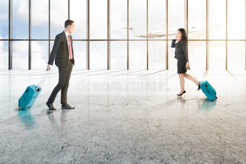 Aantrekkelijke twee Aziatische bedrijfsmensen die met mobiele telefoon en blauwe koffers op de luchthavenzaal lopen stock foto's