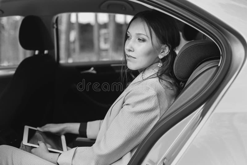 Aantrekkelijke uitvoerende vrouwelijke manager die met een tablet in een achterbank van een auto werken stock afbeeldingen