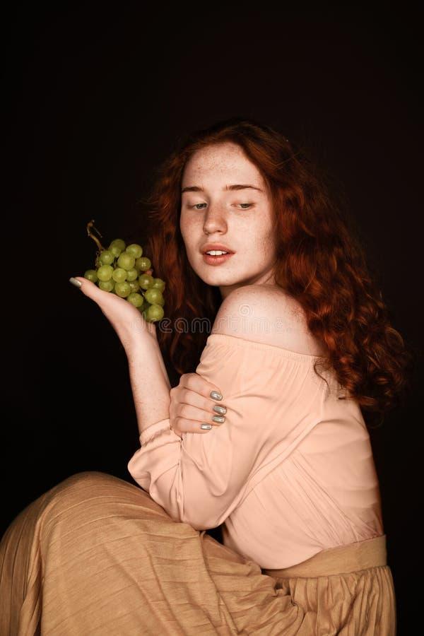 Aantrekkelijke verleidelijke roodharigevrouw die verse groene druiven houden, royalty-vrije stock foto
