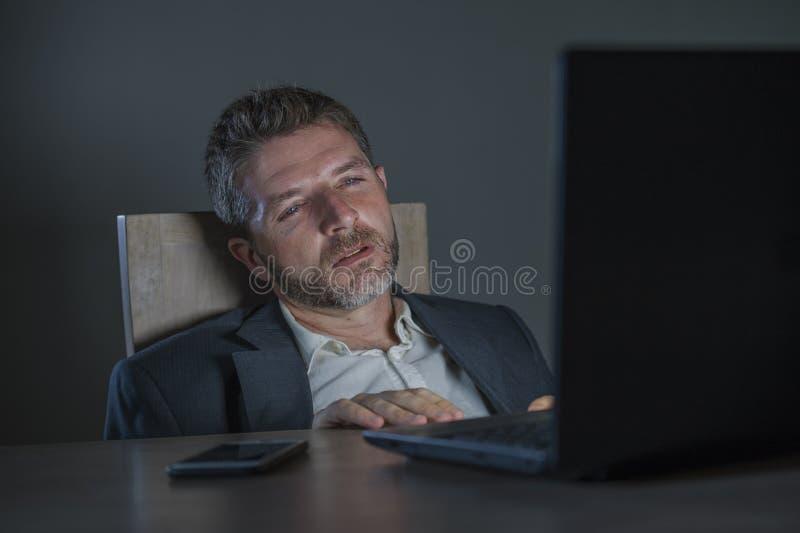 Aantrekkelijke verspilde en vermoeide ondernemersmens die laat werken - de nacht bij bureaulaptop computerbureau putte en slaperi royalty-vrije stock fotografie