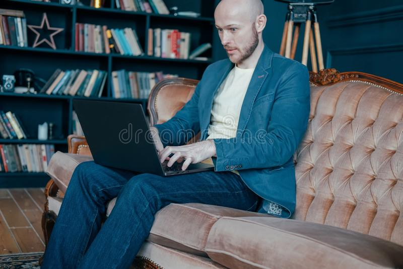 Aantrekkelijke volwassen succesvolle verraste kale mens met baard in kostuum die bij laptop aan zijn rijk kabinet werken stock afbeeldingen