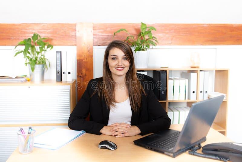 Aantrekkelijke vrij jonge onderneemster die met laptop in haar werkstation werken stock afbeelding