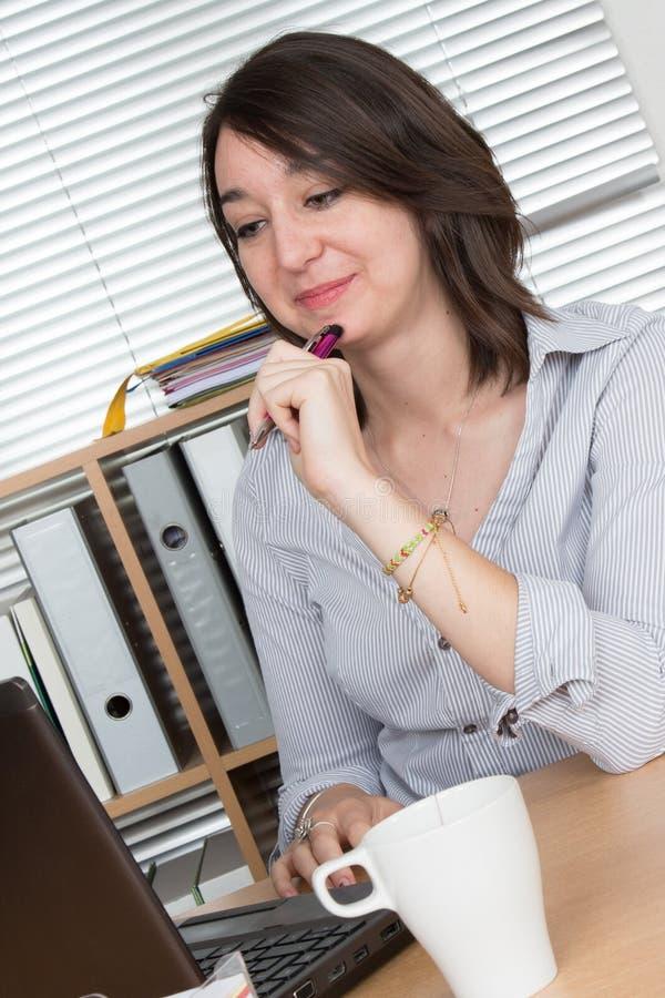 Aantrekkelijke vrouw bij modern bureau die met laptop werken die computer bekijken stock foto's