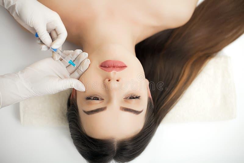 Aantrekkelijke vrouw bij plastische chirurgie met spuit in haar gezicht stock foto