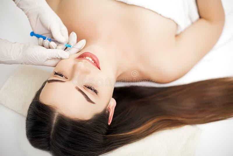Aantrekkelijke vrouw bij plastische chirurgie met spuit in haar gezicht royalty-vrije stock foto