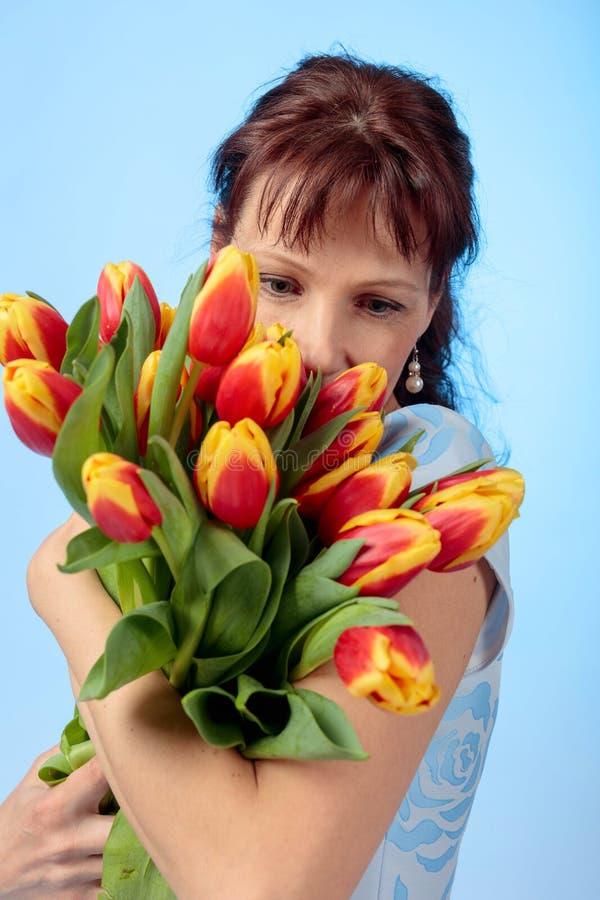 Aantrekkelijke vrouw in blauwe kleding met een boeket van rode en gele tulpen royalty-vrije stock afbeeldingen