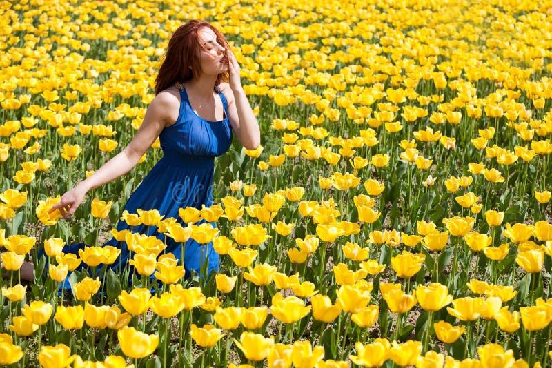 Aantrekkelijke vrouw in blauwe kleding op mooi bloemgebied royalty-vrije stock foto's