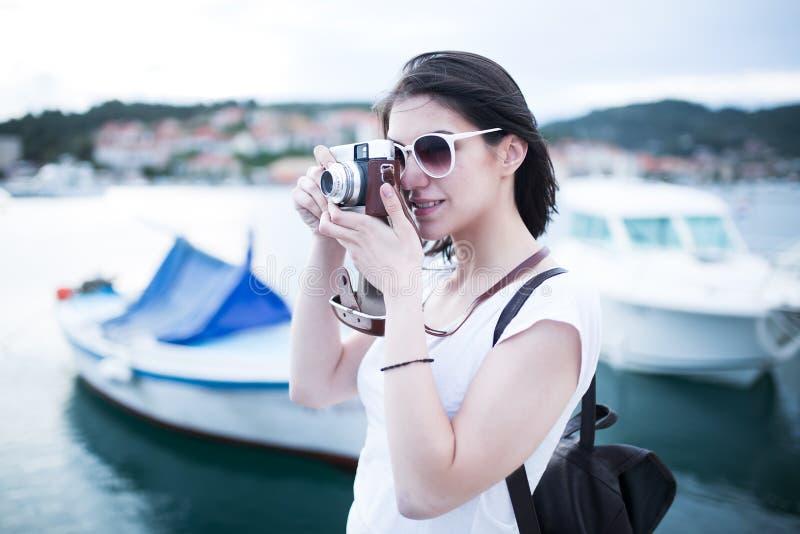 Aantrekkelijke vrouw die beelden met uitstekende retro en camera nemen die gelukkig tijdens de vakantiereis van de de zomervakant royalty-vrije stock afbeelding
