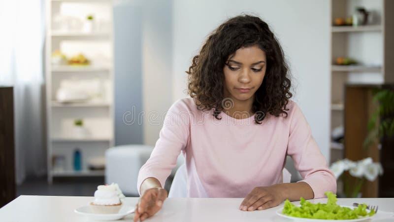 Aantrekkelijke vrouw die droevig salade over cake, gewichtscontrole, dieetvoeding kiezen royalty-vrije stock foto