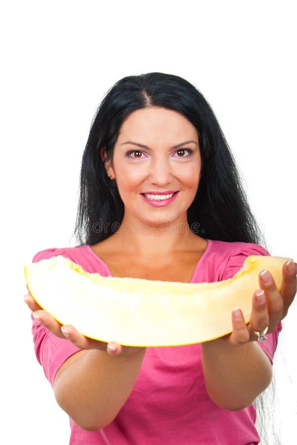 Aantrekkelijke vrouw die een plak van meloen geeft royalty-vrije stock afbeelding