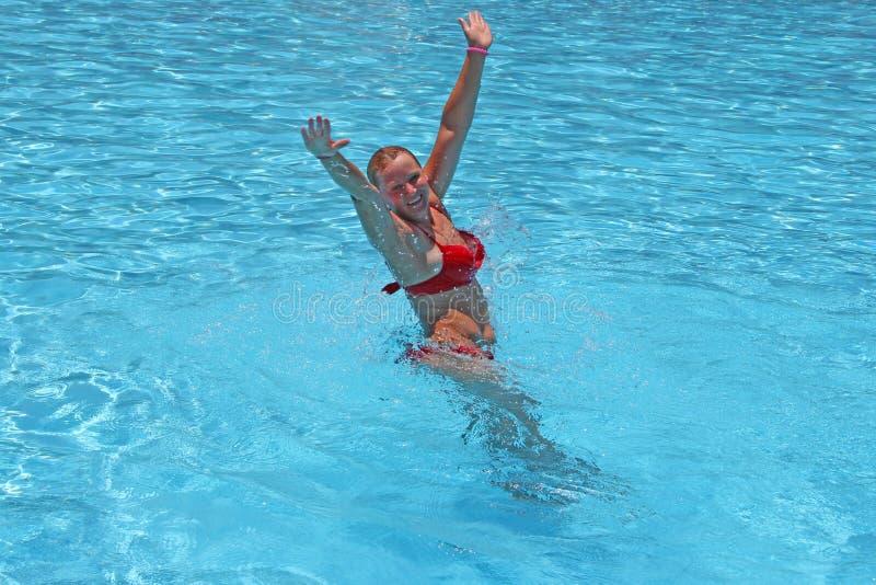 Aantrekkelijke vrouw die en in pool tijdens vakantie ontspannen zwemmen stock foto's