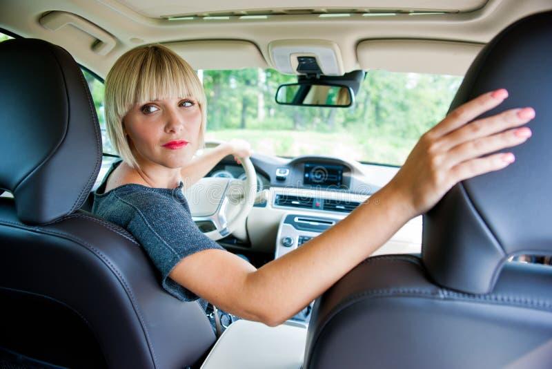 Aantrekkelijke vrouw die haar auto parkeren stock afbeelding