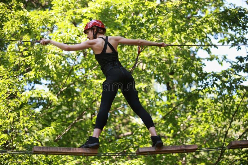 Aantrekkelijke vrouw die in het park van de avonturenkabel in veiligheidsmateriaal beklimmen royalty-vrije stock afbeelding