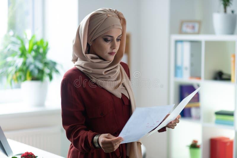 Aantrekkelijke vrouw die hijab lezings belangrijke documenten dragen stock afbeeldingen
