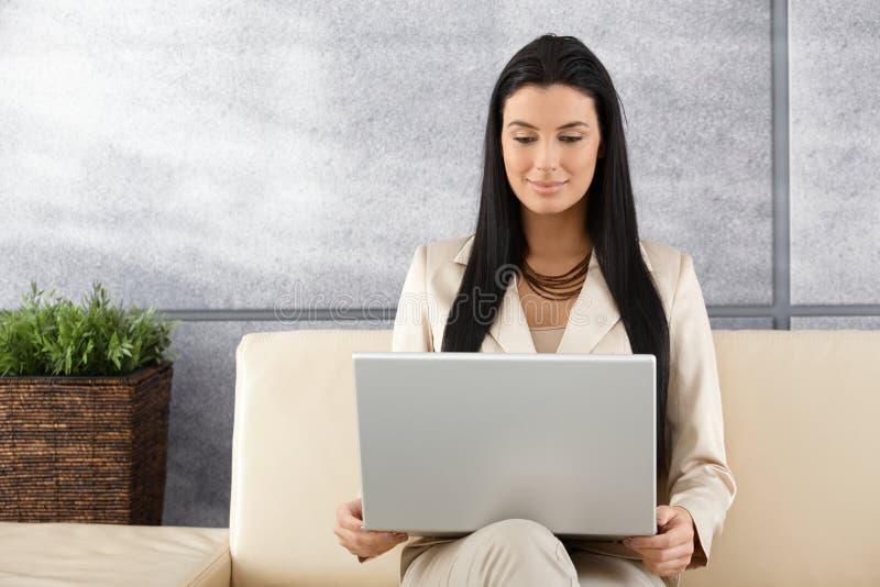 Aantrekkelijke vrouw die laptop het glimlachen gebruiken royalty-vrije stock foto's