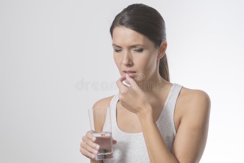 Aantrekkelijke vrouw die medicijn nemen stock foto