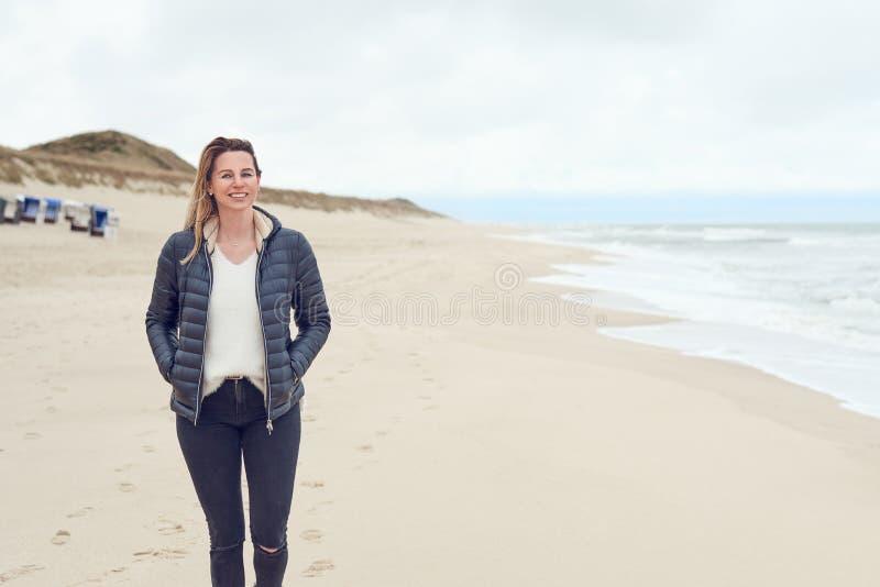 Aantrekkelijke in vrouw die op een verlaten zandig strand lopen royalty-vrije stock foto's
