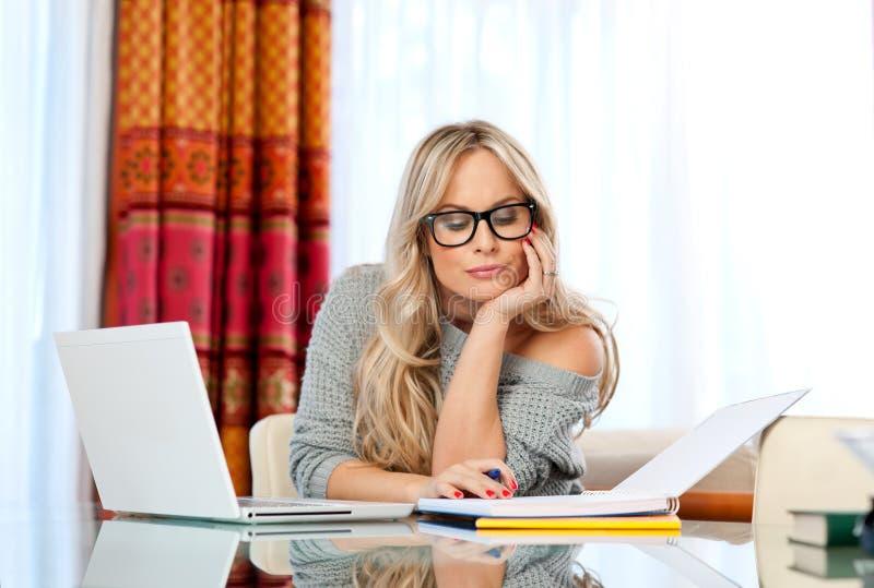 Aantrekkelijke vrouw die op laptop schrijven stock foto's