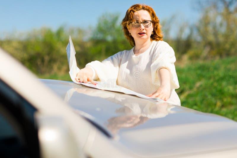 Aantrekkelijke vrouw die positie in document kaart controleren op bonnet stock foto's