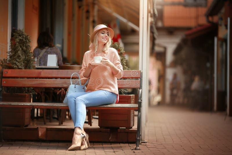Aantrekkelijke vrouw die in romantische stemming in gelukzitting bij lijst glimlachen die roze jasje dragen royalty-vrije stock foto's