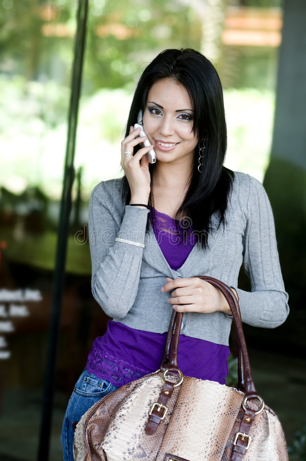 Aantrekkelijke vrouw die terwijl het gebruiken van celtelefoon glimlacht royalty-vrije stock foto's