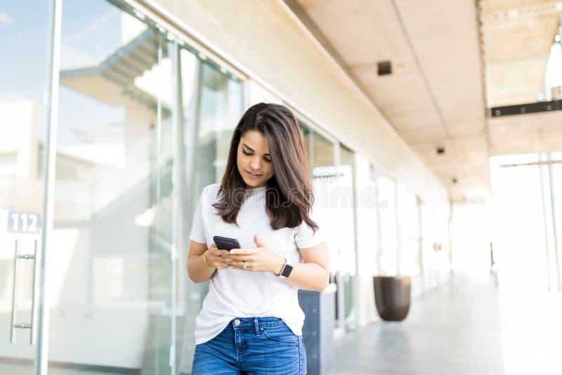 Aantrekkelijke Vrouw die Toepassing op Smartphone in Winkelende Cen gebruiken stock afbeelding