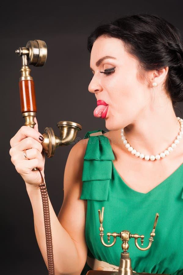 Aantrekkelijke vrouw die tong tonen in telefoon stock foto's