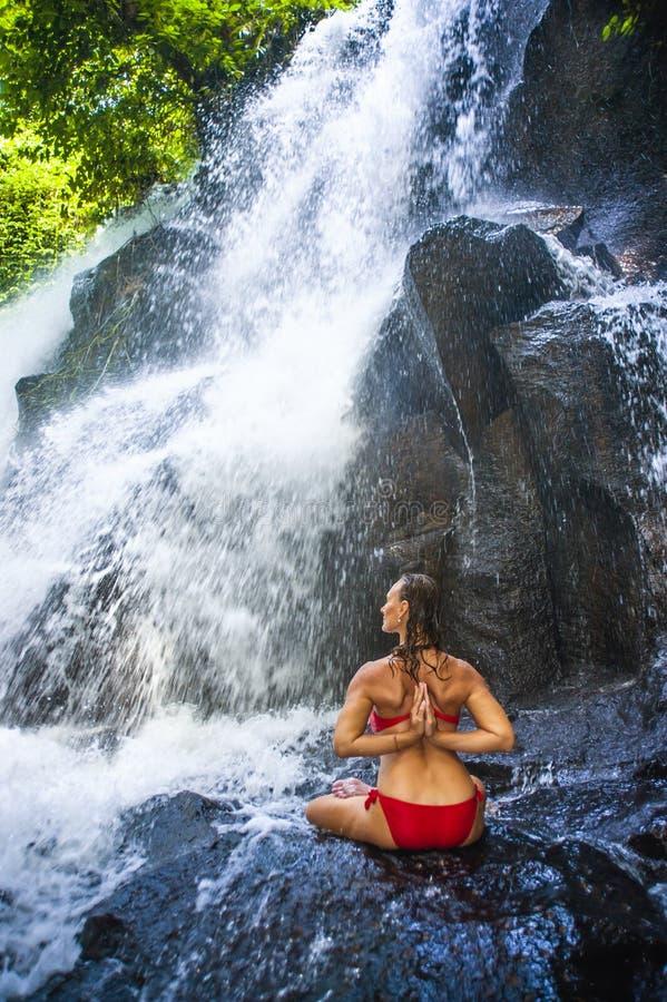 Aantrekkelijke vrouw die yogaoefening het stellen met handen op haar doen terug onder mooie tropische waterval die het natte glim stock fotografie