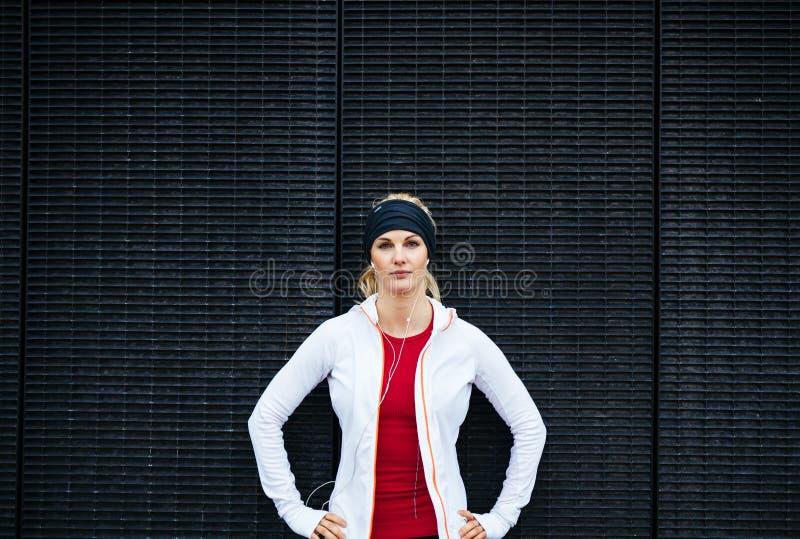 Aantrekkelijke vrouw die zeker in sportkleding kijken royalty-vrije stock afbeelding