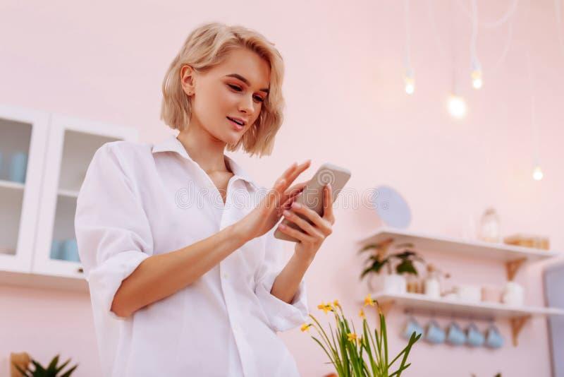 Aantrekkelijke vrouw die zich in keuken en het gebruiken van smartphone bevinden stock afbeelding