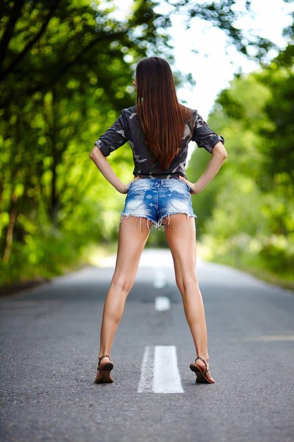 Aantrekkelijke vrouw die zich op de weg bevinden stock fotografie