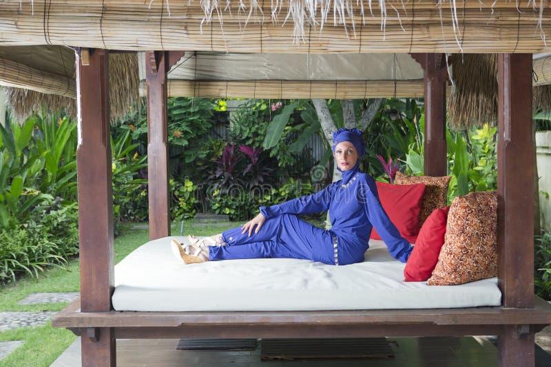 Aantrekkelijke vrouw in een Moslim swimwear burkini in gazebo voor rust in een tuin stock afbeelding