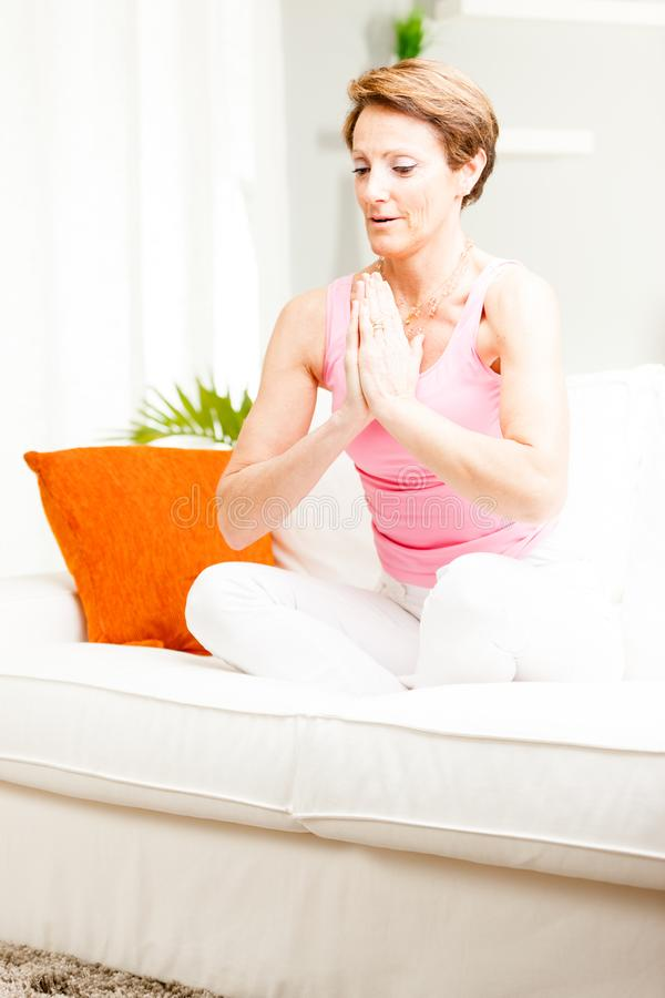 Aantrekkelijke vrouw het praktizeren yoga thuis stock afbeeldingen