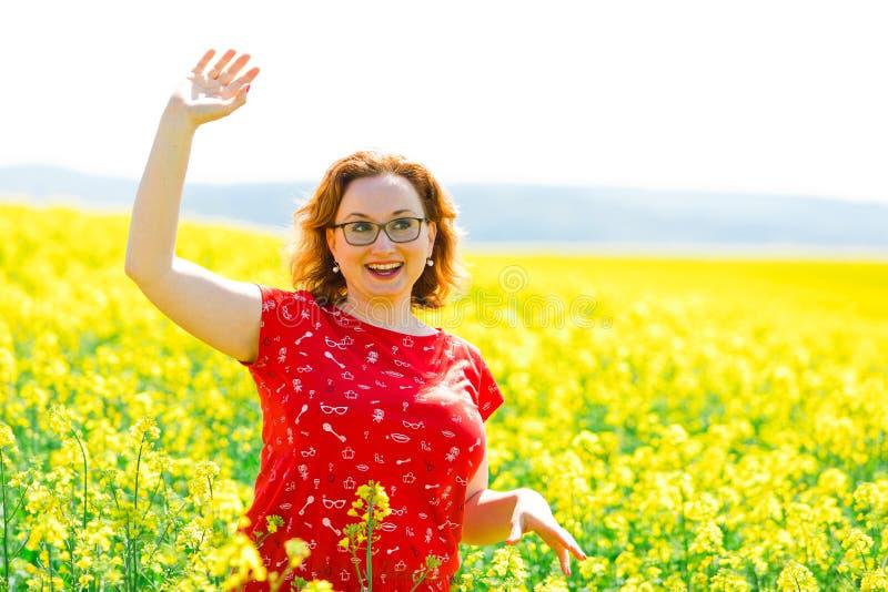 Aantrekkelijke vrouw in het rode kleding stellen op koolzaadgebied royalty-vrije stock fotografie
