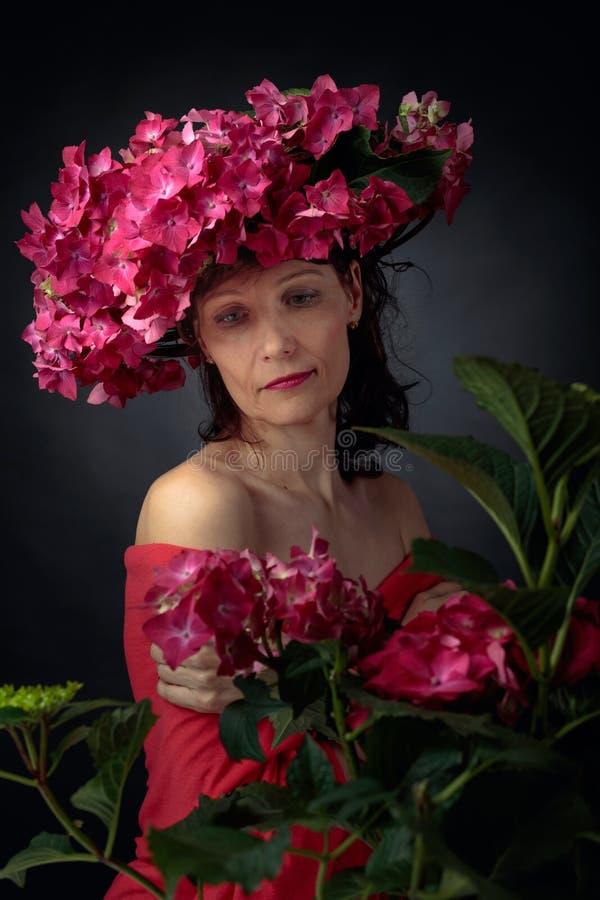 Aantrekkelijke vrouw in kroon met de bloesems van de koraalhydrangea hortensia stock foto